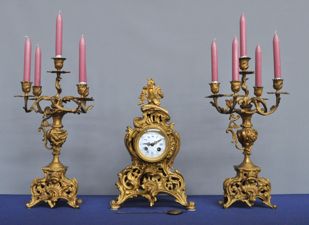 Een klokstel van verguld brons in lodewijk xv stijl bestaande uit een pendule en twee kandelaars - Stijl ligstoelen anciennes ...