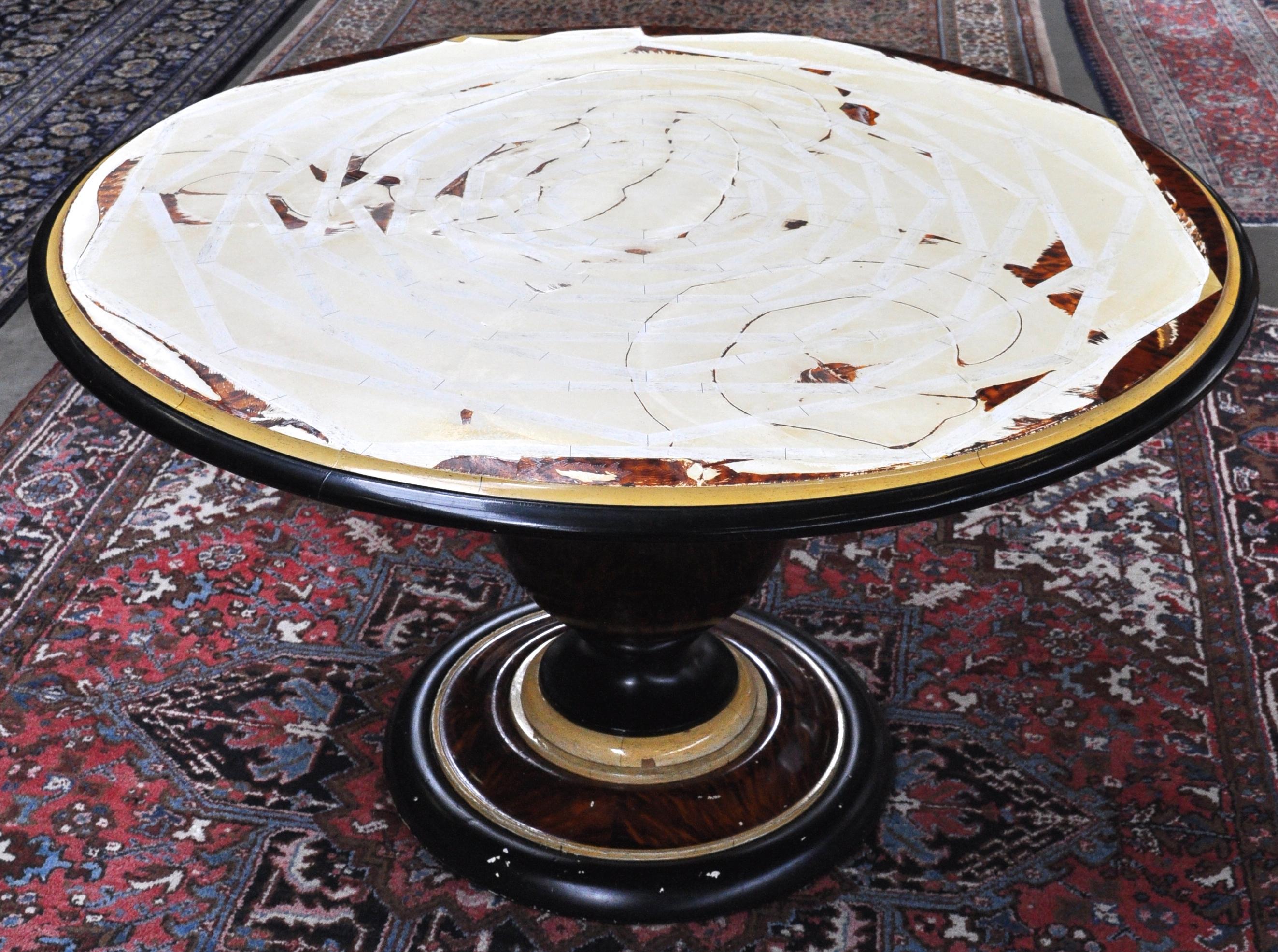 Een ronde tafel op centrale poot met imitatie schildpadfineer