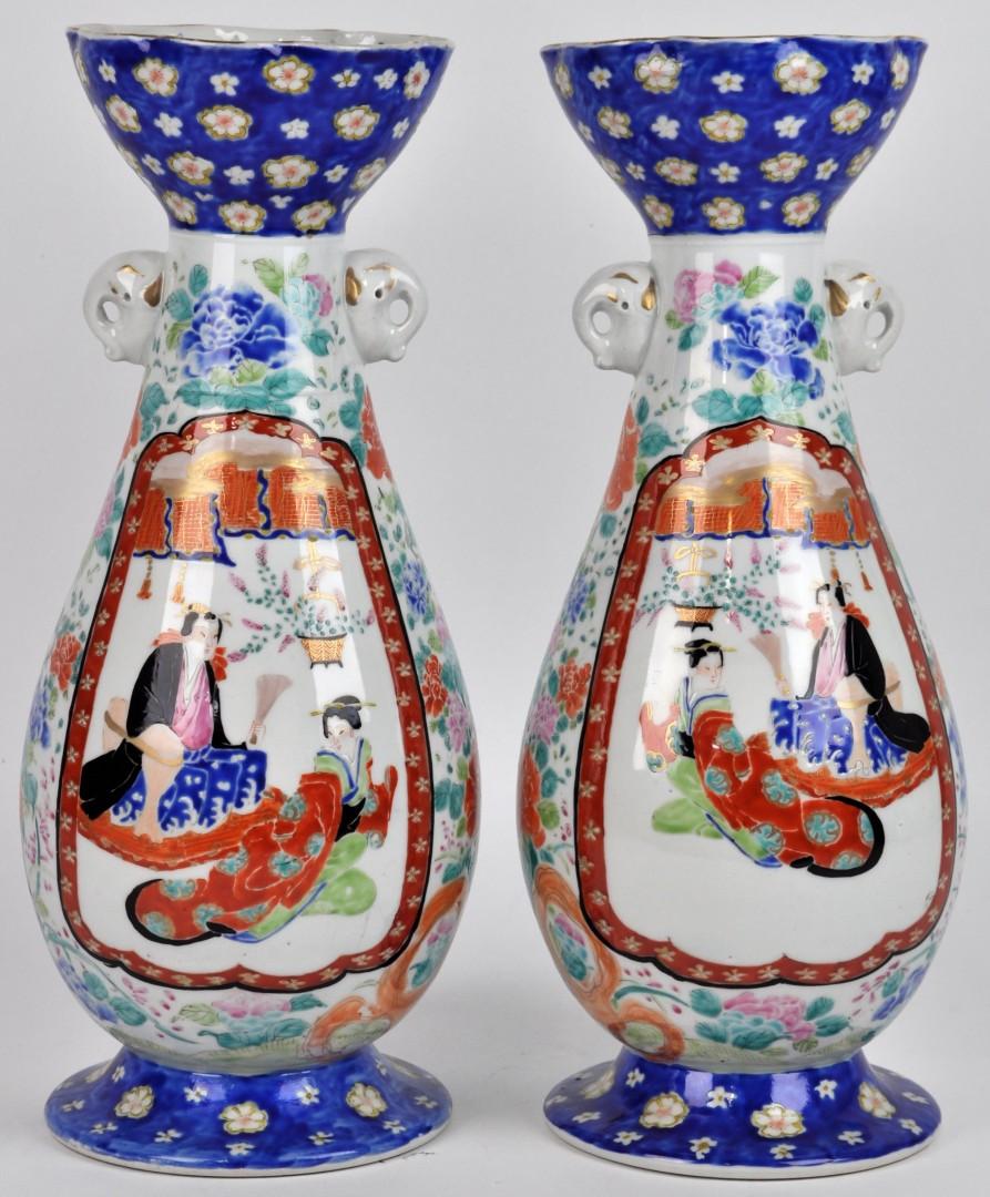 Een paar vazen van Chinees porslein met een meerkleurig decor van personages en bloemen en versierd met twee olifantjes. Onderaan gemerkt.