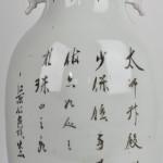 Een balustervaas van Chinees porselein met een fô-honden in ijzerrood en kaligrafische tekens in het decor. XIXde eeuw.