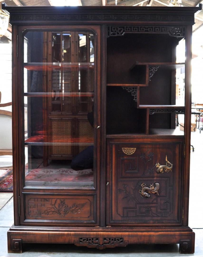 Een Chinese vitrinekast van gesculpteerd hout met aan de zijkant een paneeldeurtje onder legplankjes in etages.
