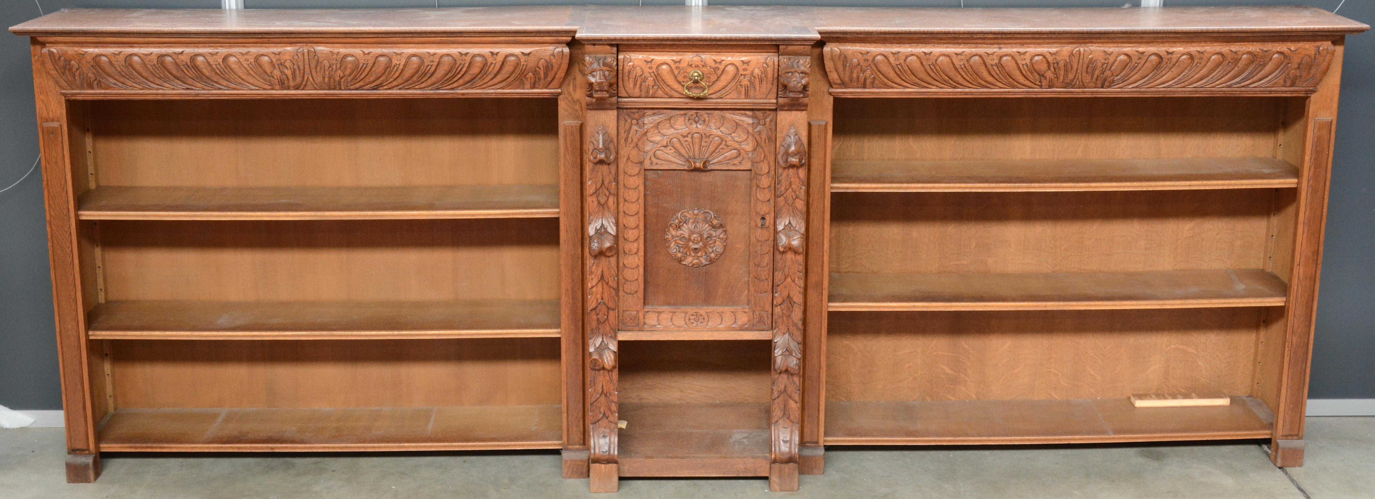 een lage boekenkast van gesculpteerd hout in mechelse renaissancestijl met centraal een paneeldeurtje en een lade