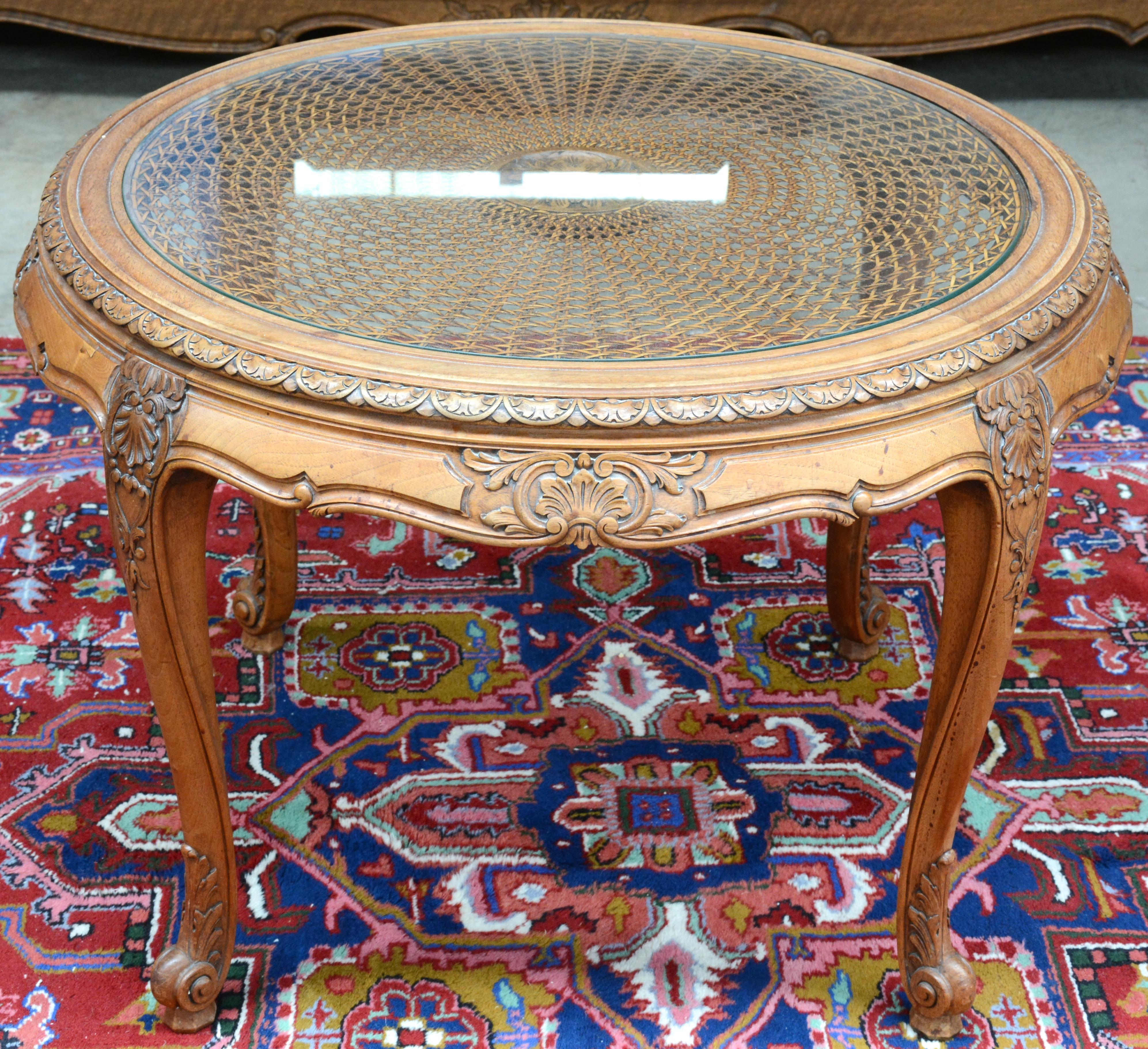 Een ronde salontafel van gesculpteerd notenhout met een gevlochten blad onder glas   u2013 Jordaens N