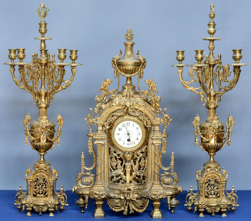Een driedelig klokstel van verguld koper in Napoleon III -stijl , bestaande uit een pendule en twee kandelaars.
