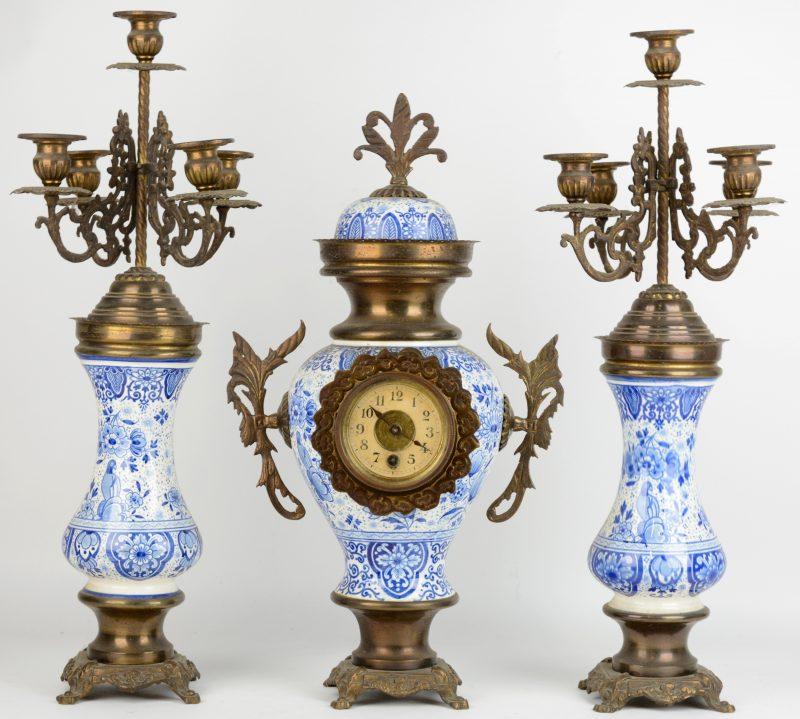 Een driedelig klokstel van koper en blauw en wit aardewerk, bestaande uit een pendule en twee kandelaars.