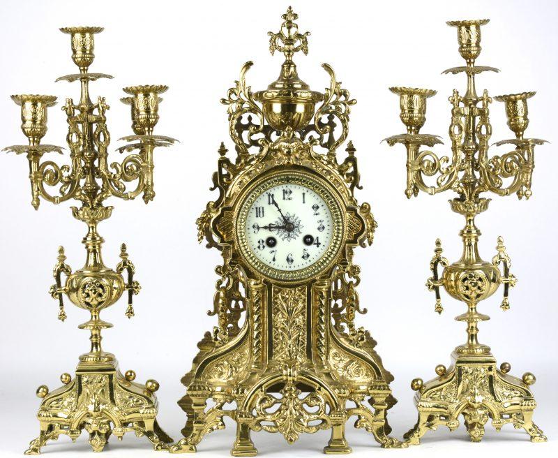 Een klokstel van geel koper, bestaande uit een pendule en twee kandelaars in Napoleon III-stijl. Eén bobeche manco.