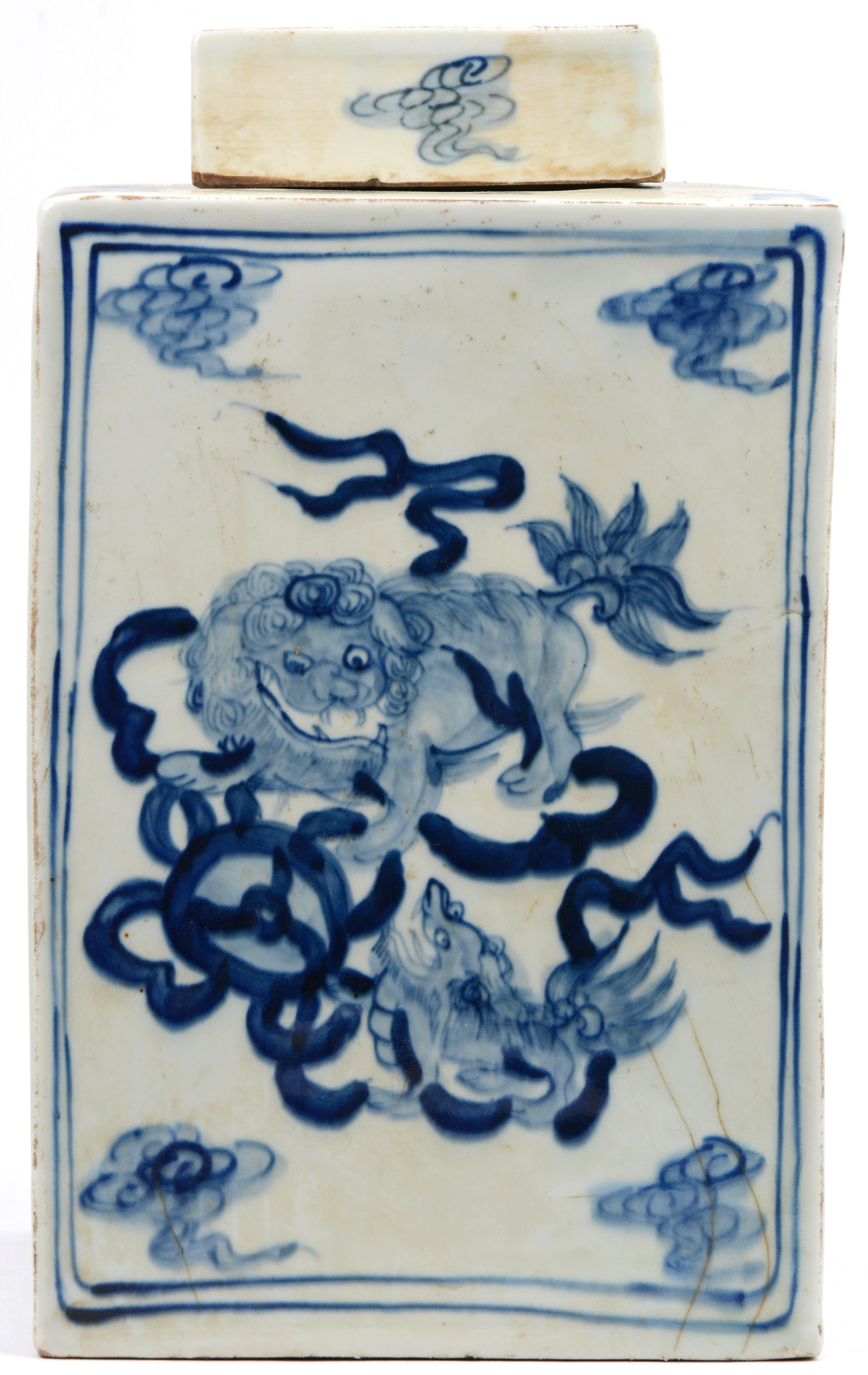Een vierkante theebus van blauw en wit Chinees porselein met Fo-honden in het decor.