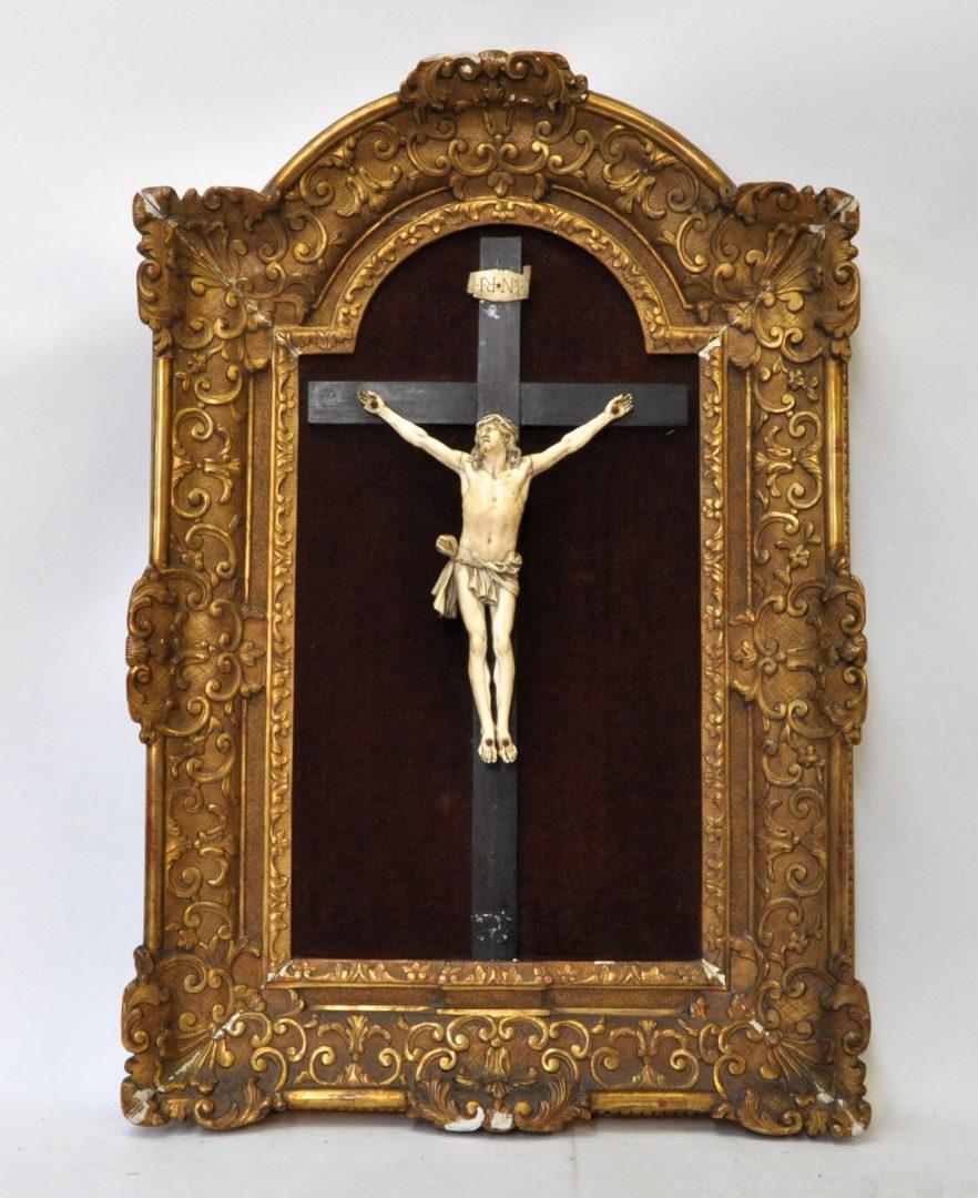 Een ivoren Corpus Christi op een zwartgelakt kruisbeeld in een vergulde kader in barokke stijl. Eén vingertje manco. XIXe eeuw.