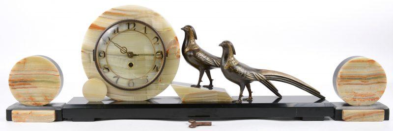 Een driedelig klokstel van onyx en zwart marmer, versierd met twee fazanten van zamak. Tijdperk art deco.