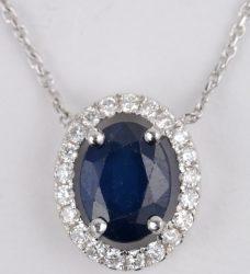 Een 18 karaats wit gouden ketting met hanger bezet met diamanten met een gezamenlijk gewicht van ± 0,21 ct. en een saffier van ± 1,14 ct.