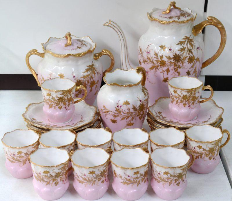 Een theeservies van roze en wit Limogesporselein met een verguld decor van bladeren, bestaande uit een theepot, suikerpot, melkkannetje en twaalf kopjes met schoteltjes. Gemerkt.