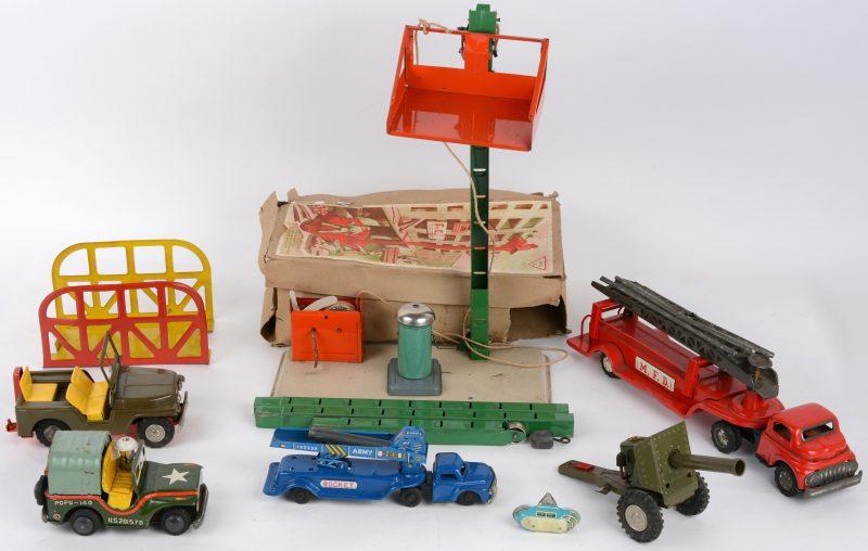 Een lot blikken speelgoed, bestaande uit twee legerjeeps, waarvan één met een artilleriegeschut, een brandweerwagen, een wagen met raketlanceerder, een brug en een kraan.