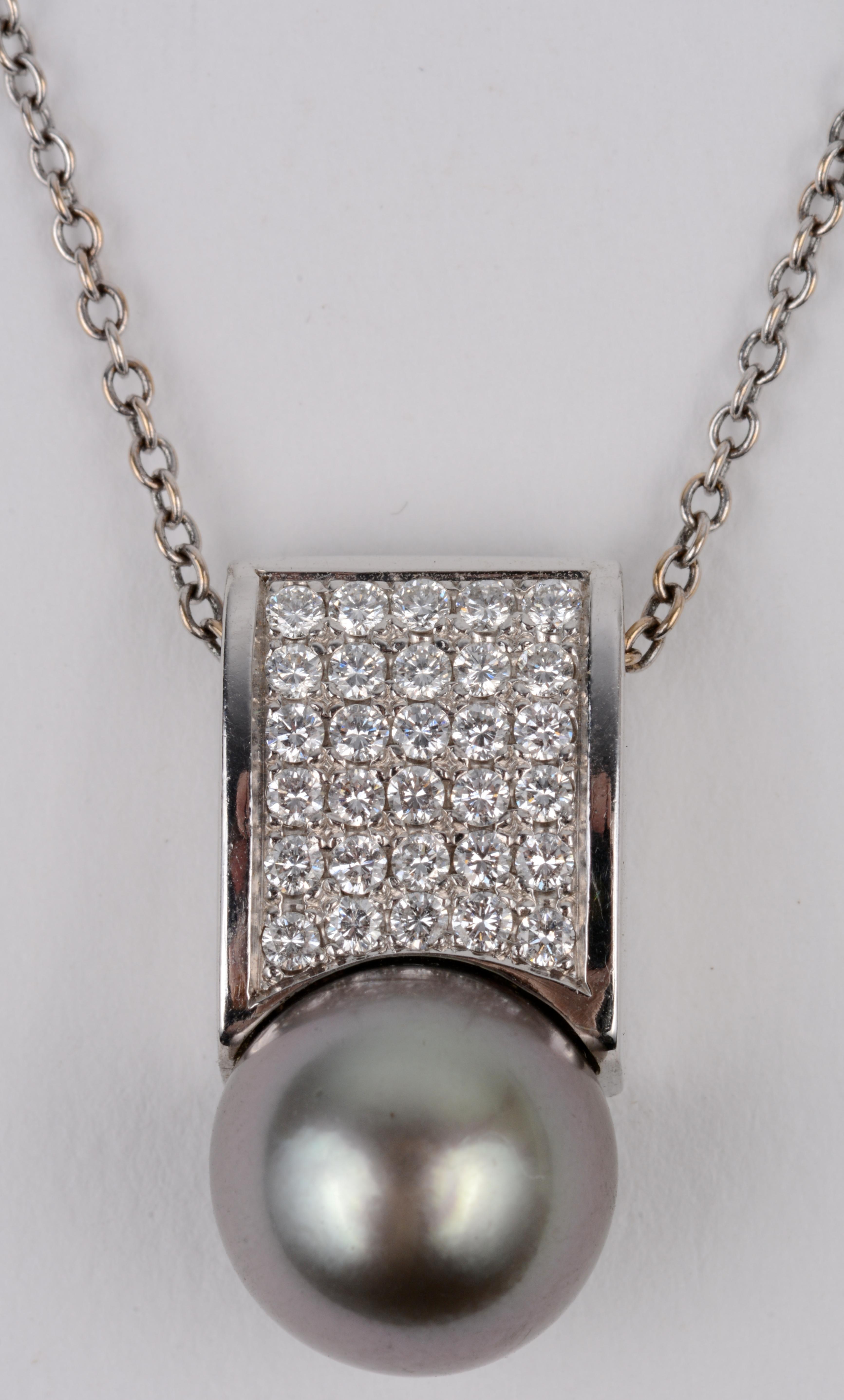 Een 18 karaats wit gouden ketting met hanger bezet met briljanten met een gezamenlijk gewicht van ± 0,45 ct. en een grijze parel.