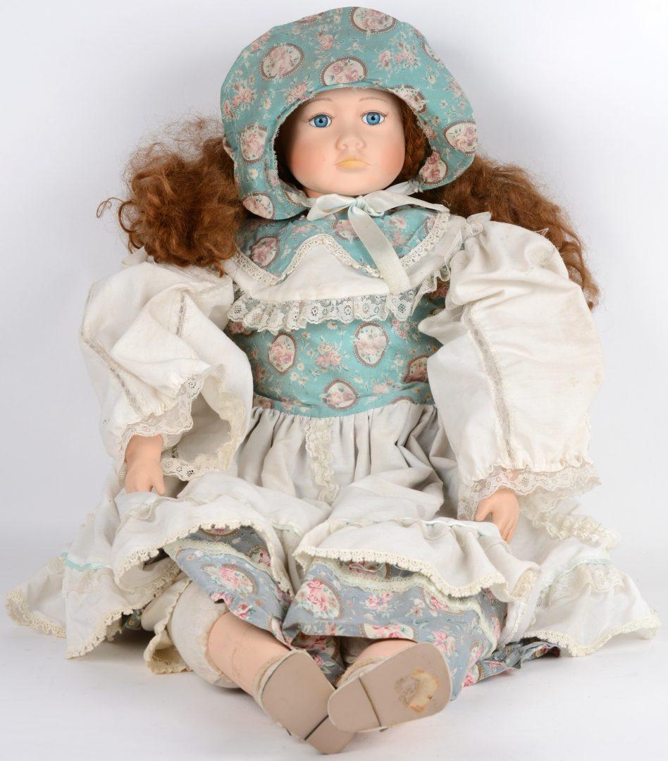 Een grote antieke pop met porseleinen hoofd en handjes.