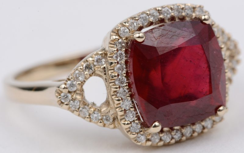 Een 18 karaats geel gouden ring bezet met diamanten met een gezamenlijk gewicht van ± 0,50 ct. en één centrale bewerkte robijn van ±4,50 ct.