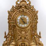 Een driedelig klokstel van verguld brons in Napoleon III-stijl, bestaande uit een pendule en twee kandelaars met telkens vijf lichtpunten.