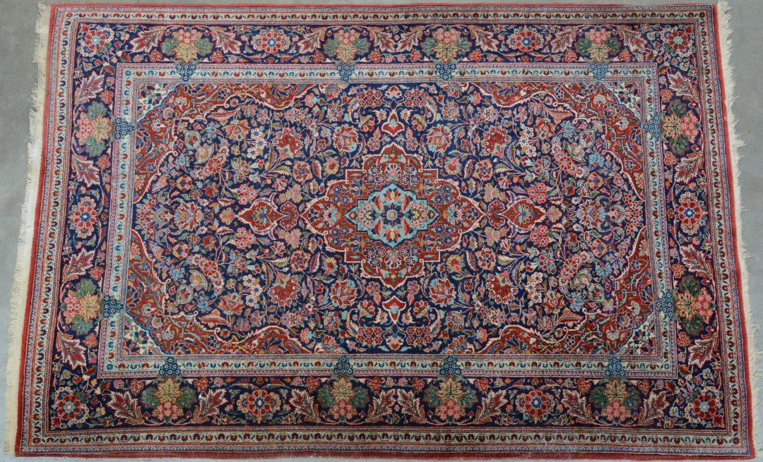 Een handgeknoopt Perzisch karpet van katoen en wol.