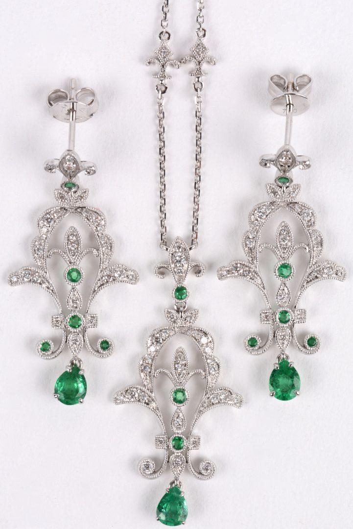 Een 18 karaats wit gouden ketting met hanger en bijpassende oorbellen bezet met briljanten met een gezamenlijk gewicht van ± 1 ct. en smaragden met een gezamenlijk gewicht van ± 1 ct.