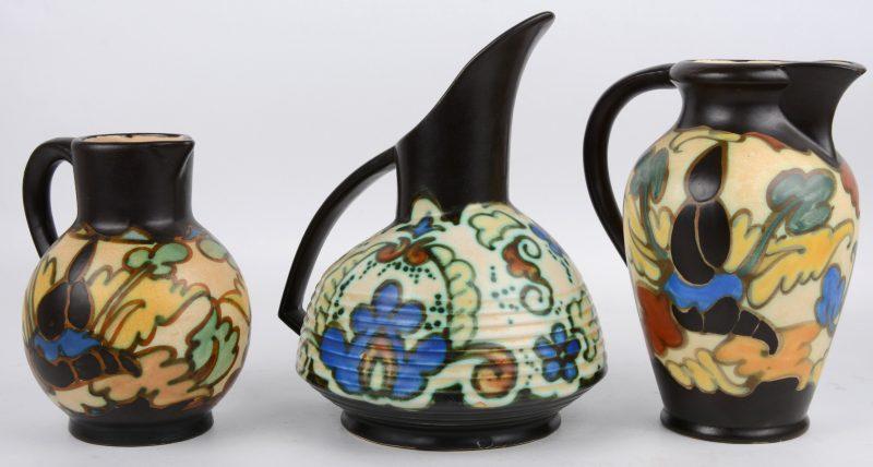 Een lot polychroom aardewerk bestaande uit drie schenkkannen.
