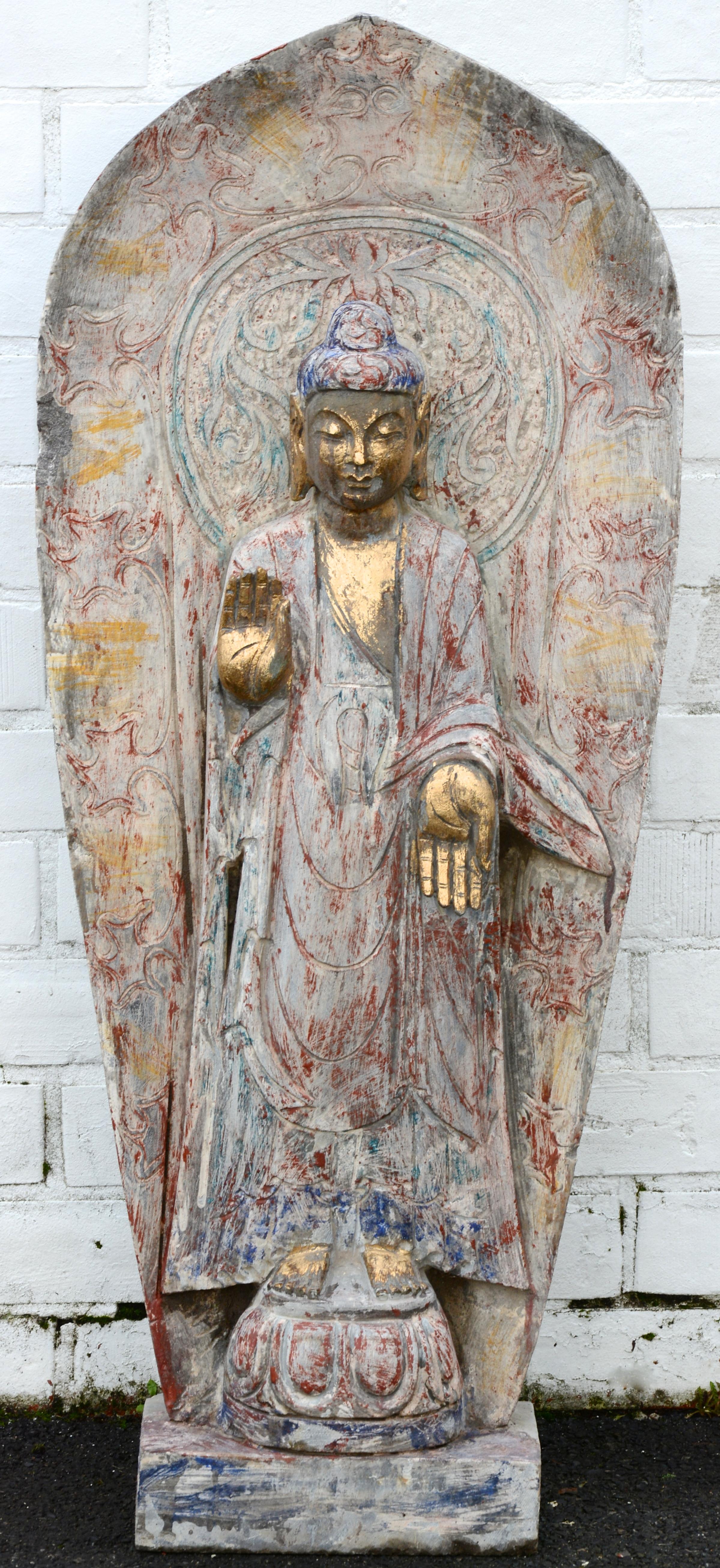 Stenen beeld van Boeddha in een schrijn. Sporen van polychromie.