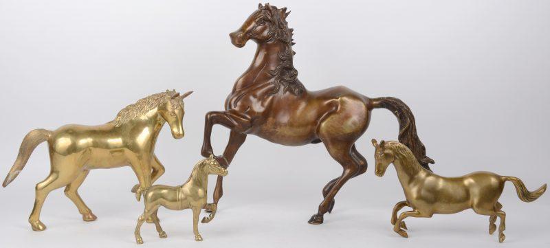 Een lot van vier bronzen paarden van verschillende groottes.