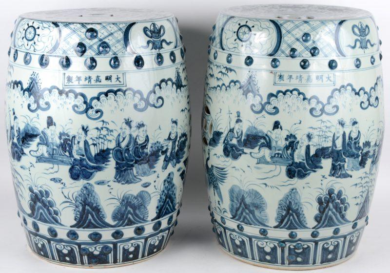 Een paar Chinese tuinstoeltjes van blauw en wit porselein met een decor van personages in een landschap.