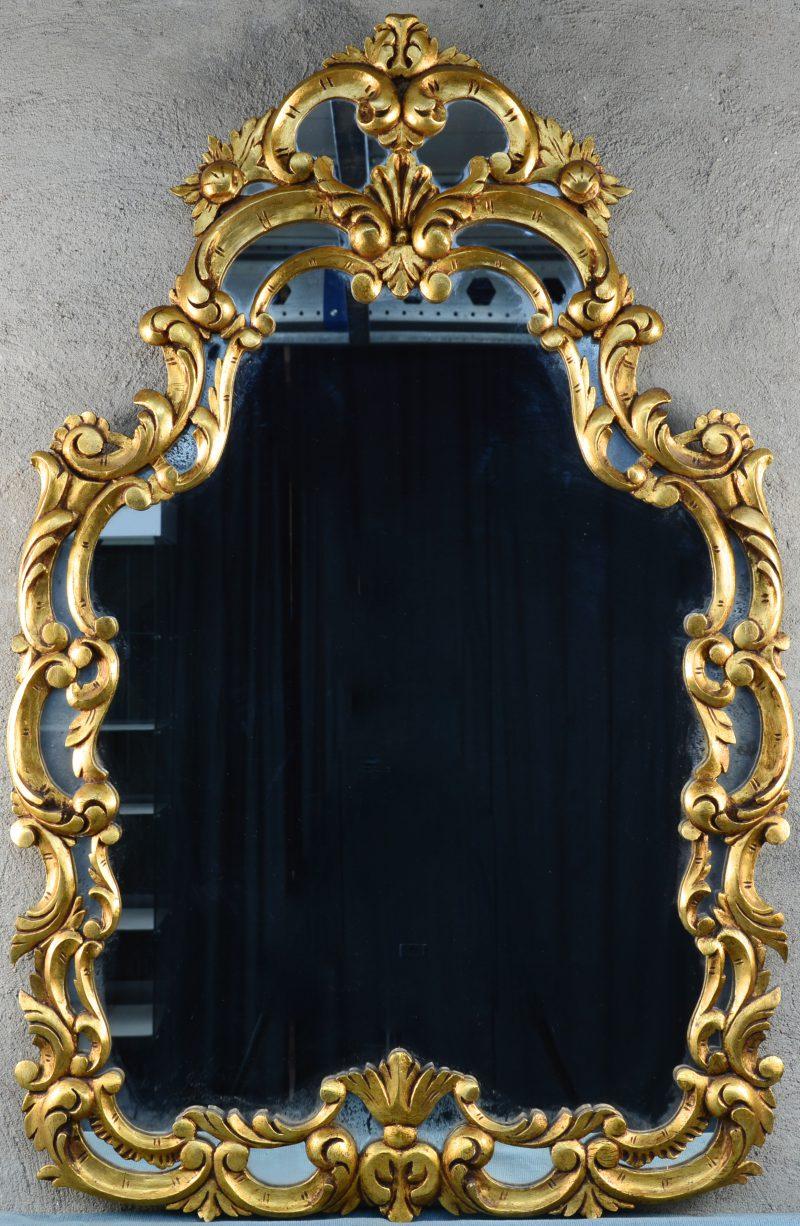 Een spiegel van gesculpteerd en goudgepatineerd hout in rococostijl.