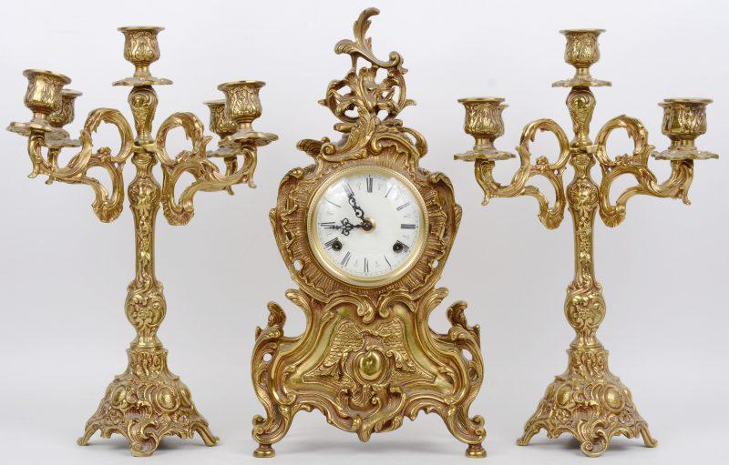 Een driedelig klokstel van verguld brons in Lodewijk XV-stijl, bestaande uit een pendule en twee kandelaars met telkens vijf lichtpunten.