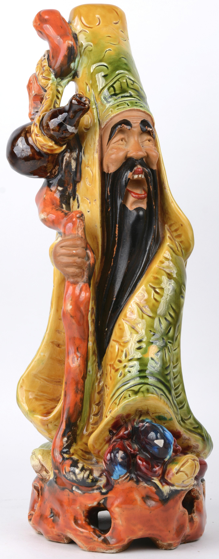 Een Chinese godheid van meerkleurig aardewerk. Achteraan gesigneerd. Gerestaureerd.