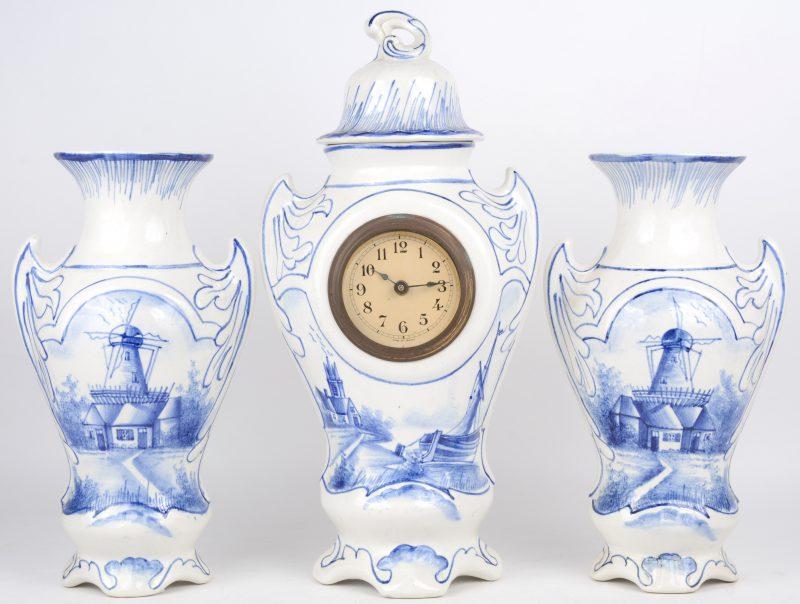 Een driedelig klokstel van blauw en wit aardewerk, bestaande uit een pendule en twee siervazen, Frans werk.