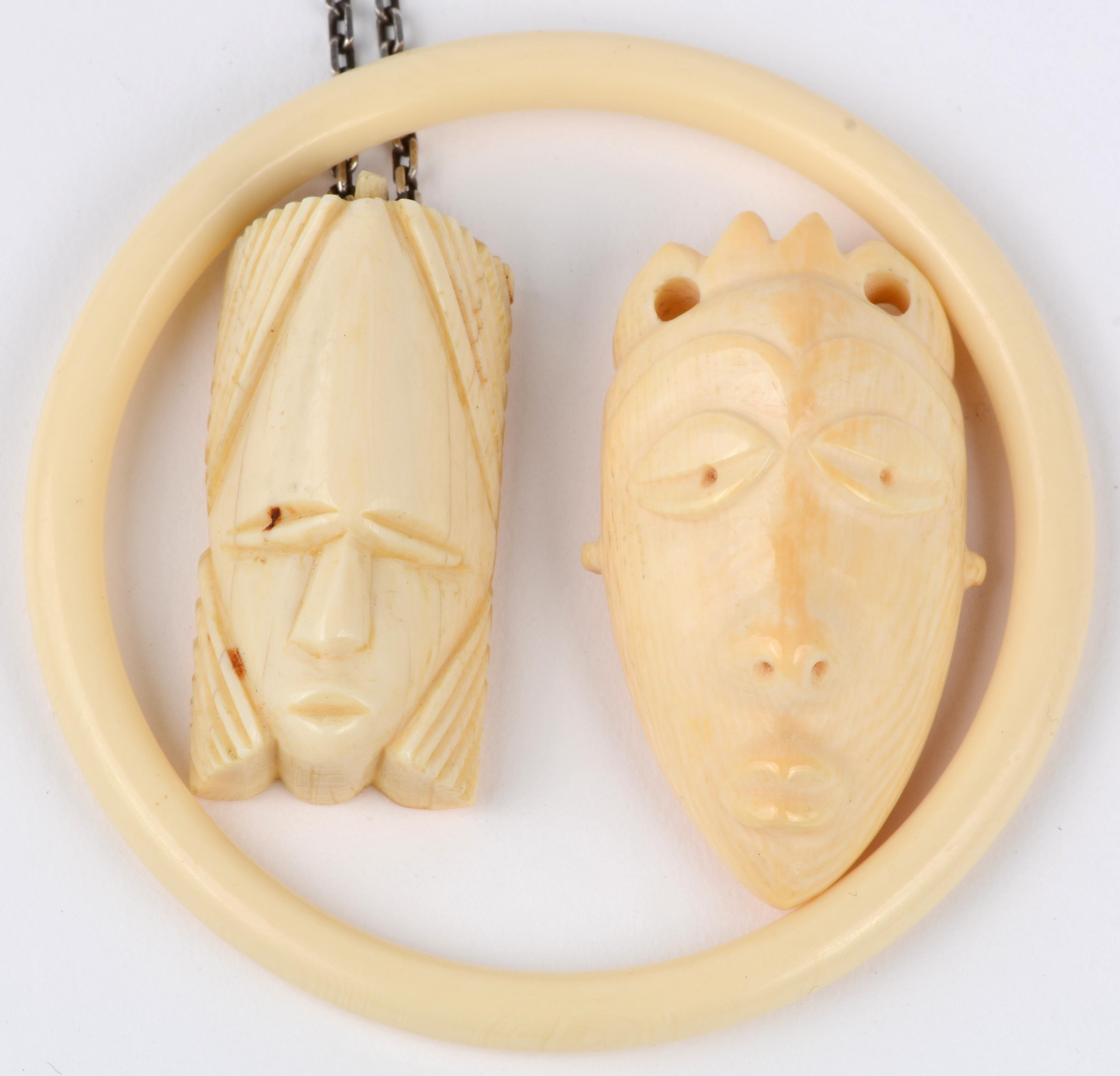 Een slavenarmband en twee hoofden als hanger van ivoor.