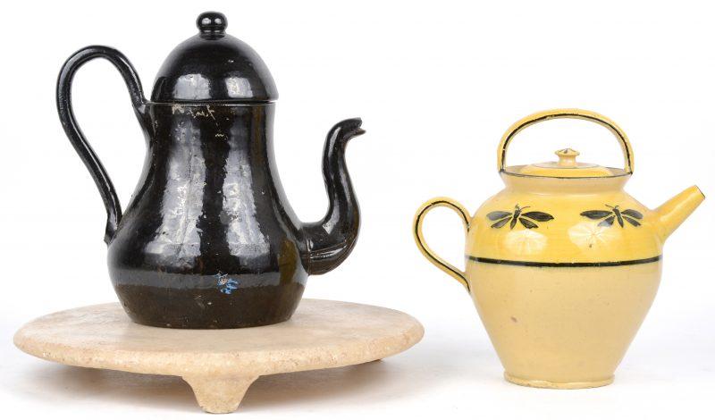 Twee verschillende aardewerken theepotten met resp. zwart en geel glazuur. We voegen er een rond albasten blad aan toe.