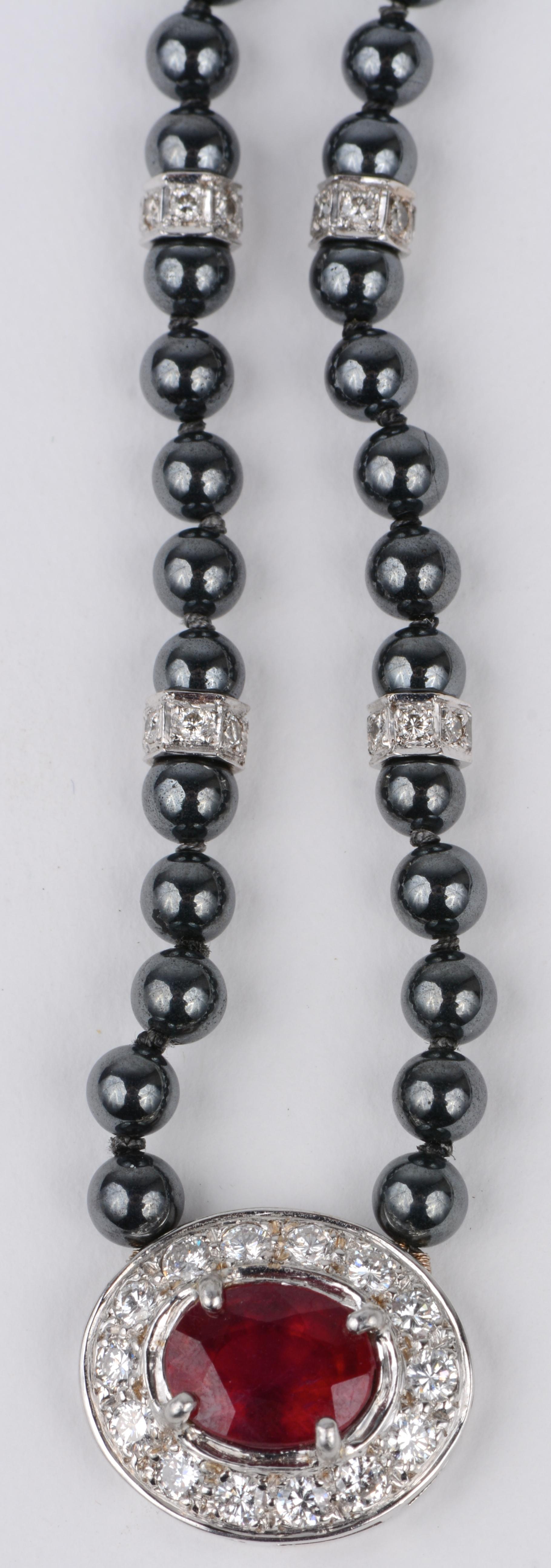 Een parelhalssnoer van hematiet met 18 karaats wit gouden tussenstukken en hanger bezet met diamanten met een gezamenlijk gewicht van ± 1 ct. en een centrale robijn van ± 2,45 ct.