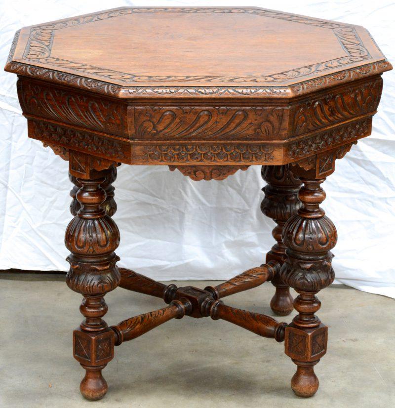 Een achthoekige bijzettafel van gebeeldhouwd eikenhout in renaissancestijl met vier poten in kruisverbinding.