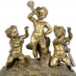 Een schouwpendule van arduin in Napoleon III-stijl, versierd met verguld brons en bovenaan getooid met drie musicerende putti.  De wijzerplaat gemerkt. Met slinger en sleutel.