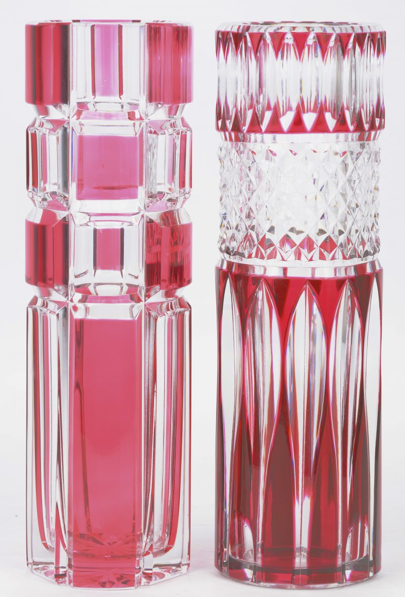 Twee verschillende cilindervazen van geslepen kleurloos en roze kristal. Beide gemerkt.