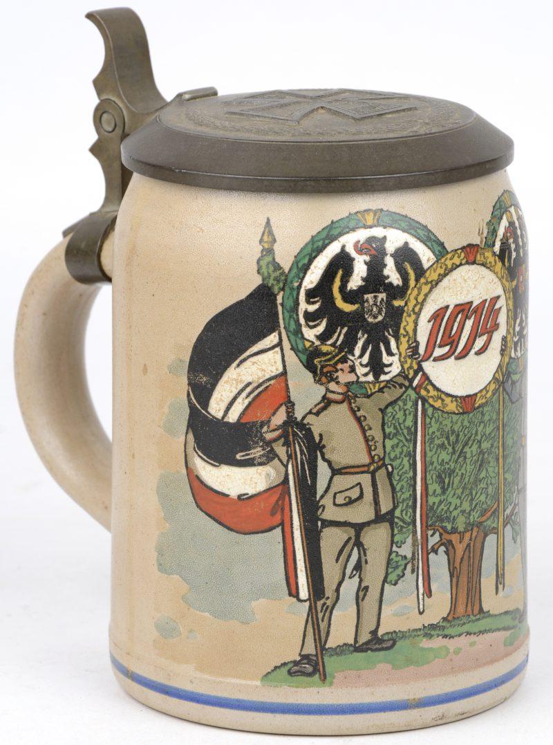 Een Duitse bierkruik van aardewerk met een meerkleurig militair decor ter ere van 1914 met een ijzeren kruis op het tinnen deksel.
