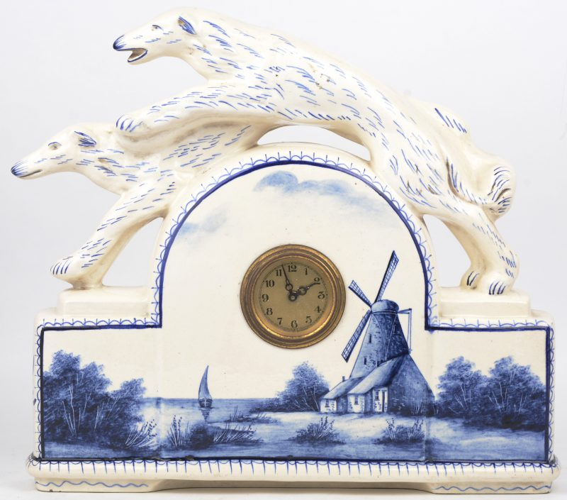 Een aardewerken pendule, bovenaan getooid met twee windhonden en met een blauw op wit decor van een molen in een landschap. Achteraan gemerkt.