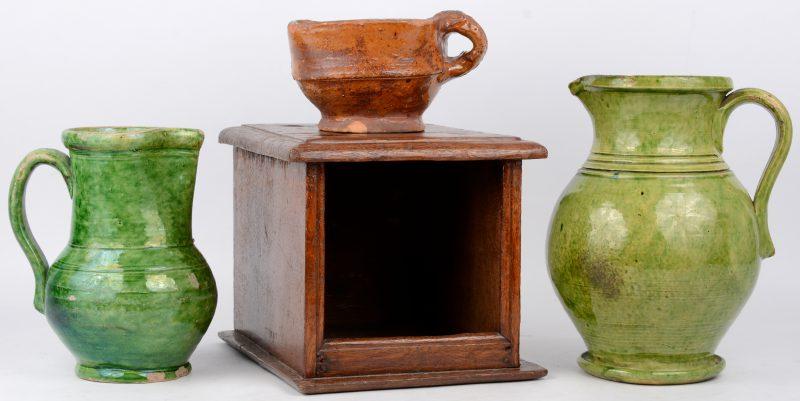 Een lot Vlaams aardewerk, bestaande uit twee kruiken en eeen voetstoofje met houten bakje. Omstreeks 1800.