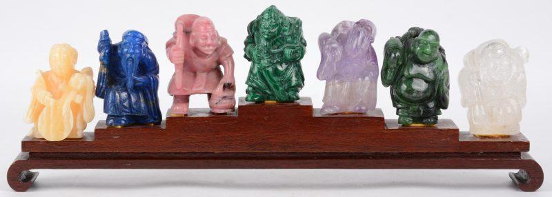 De zeven geluksgoden van diverse pietra dura. Chinees werk. Op gemeenschappelijke houten sokkel. Respectievelijk: Citrine, Lapis Lazuli, Rhodoniet, Malachiet, Amethist, Jade en Bergkristal.