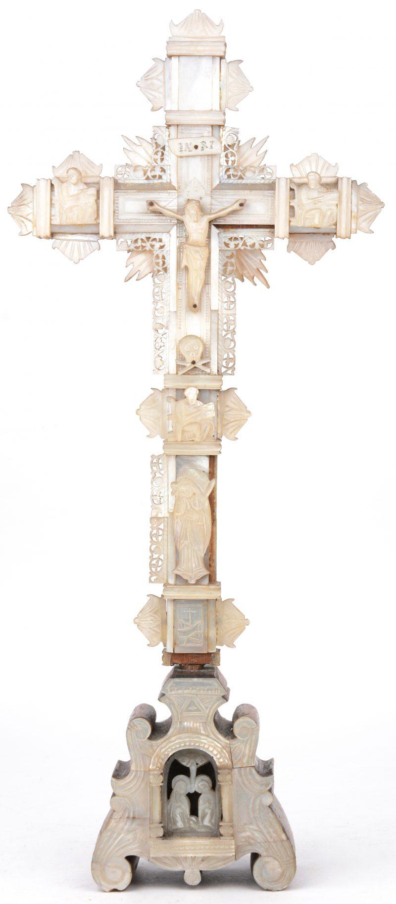 Een kruisbeeld van hout en parelmoer met achteraan zestien reliekhoudertjes. Omstreeks 1900. Vooraan een stukje manco.