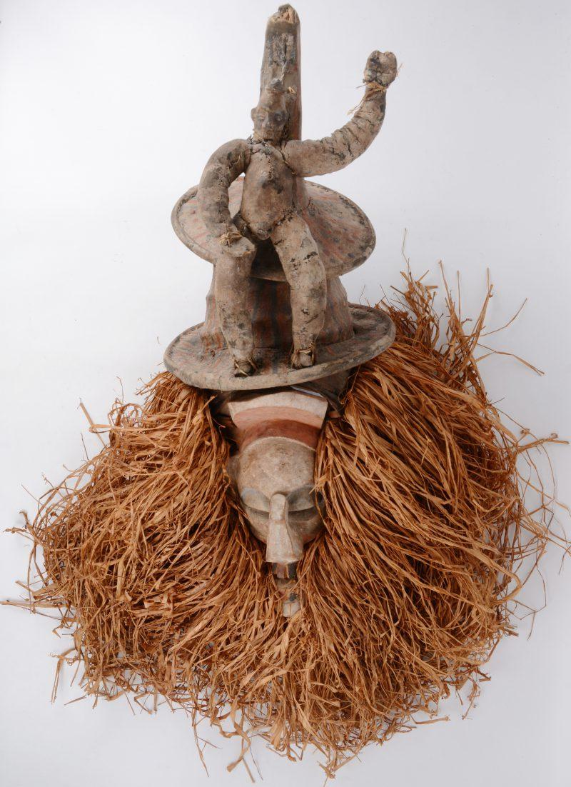 Een Afrikaans masker van gepolychromeerd hout met een hout, getooid met een poppetje.
