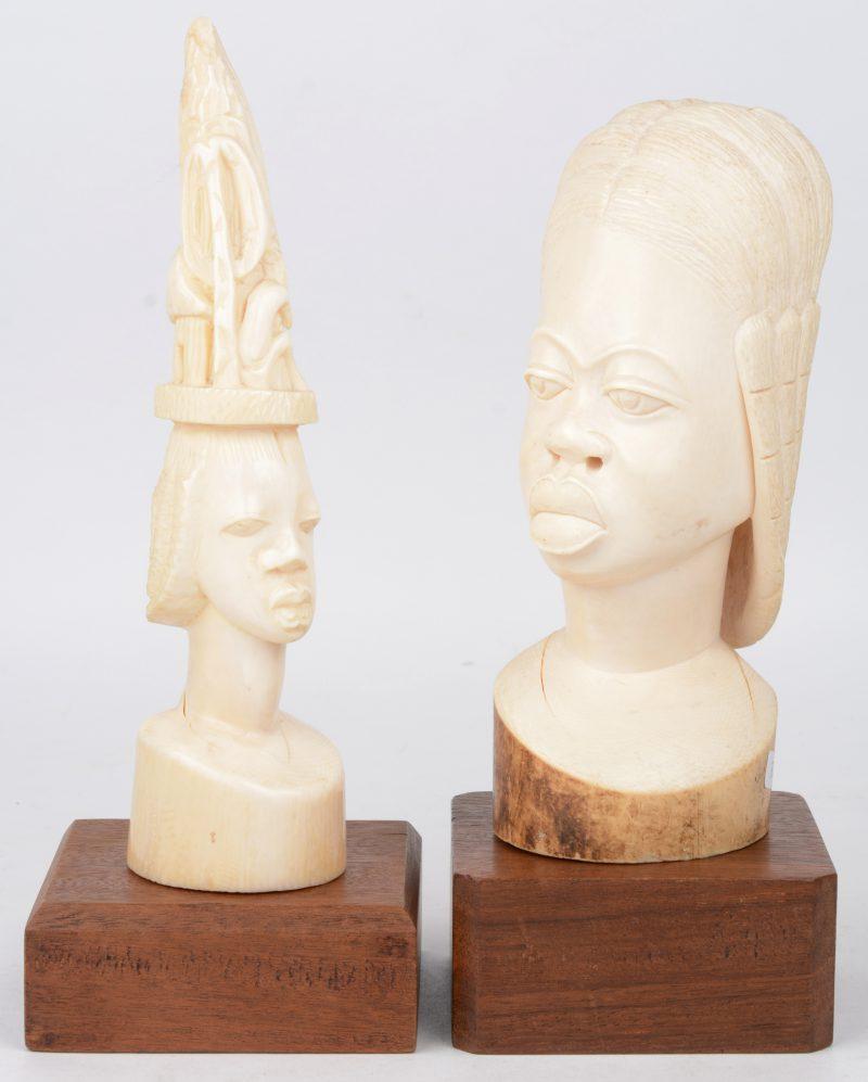 Twee Afrikaanse voruwenbustes van gesculpteerd ivoor op houten sokkeltjes.