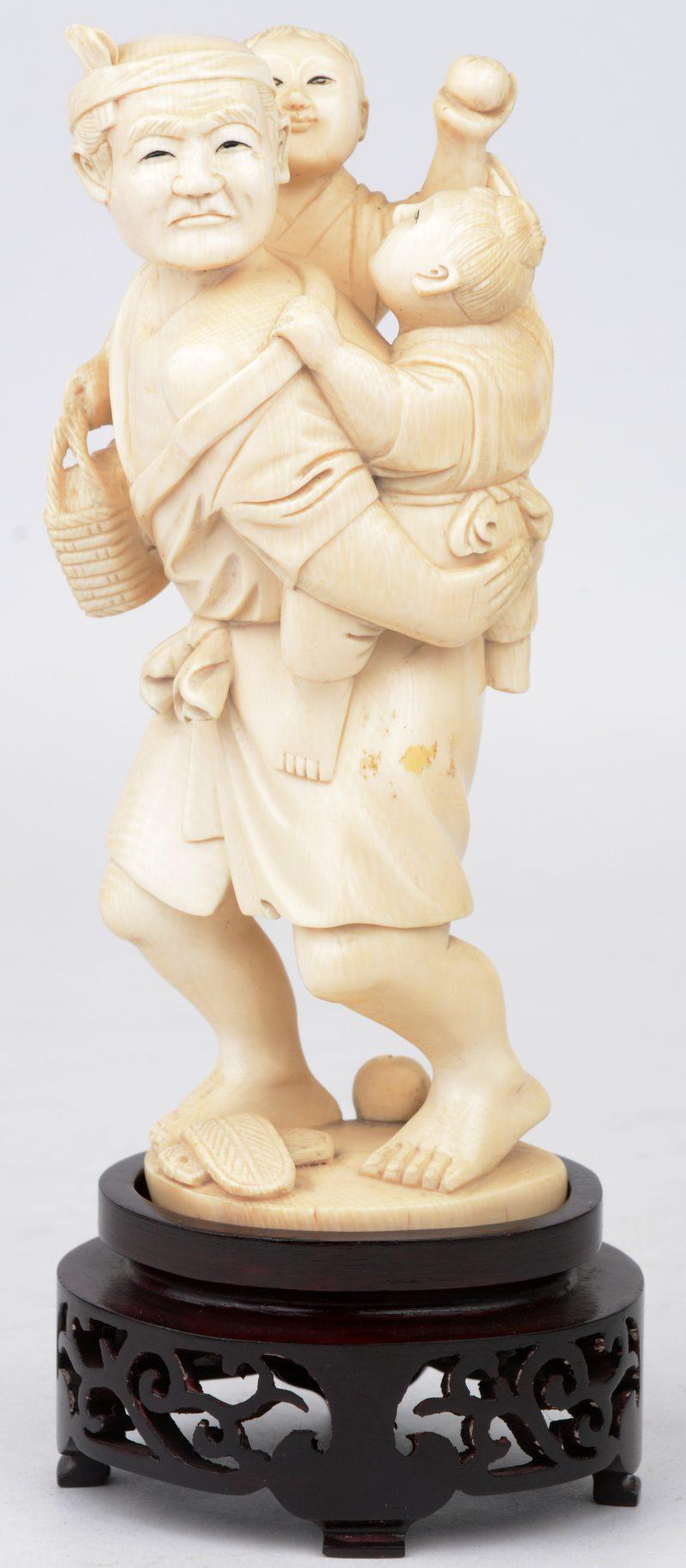"""""""Man met kinderen"""". Een beeldje van gesculpteerd Chinees ivoor. Op houten voetstukje."""