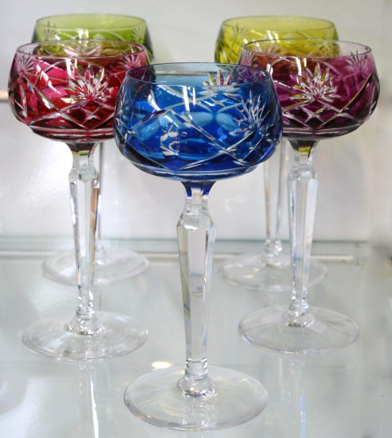 Een reeks van vijf glazen op voet van geslepen kristal in verschillende kleuren. Onderaan gemerkt.