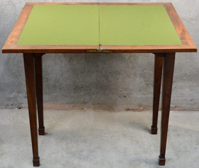 Een kaarttafel van mahoniehoutfineer met een klapblad en vier tapse poten. Vilt recent vervangen.