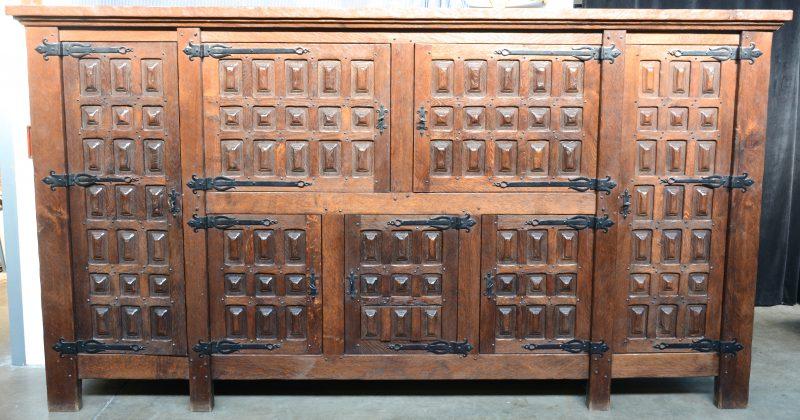Een grote eikenhouten kast in Spaanse renaissancestijl met zes paneeldeuren, versierd met cassettes in smeedijzeren hengsels en met drie laden.