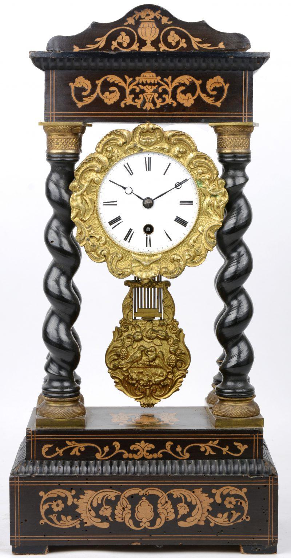 Een Napoleon III kolompendule van zwartgelakt hout en verguld messing versierd met marquetterie. Met sleutel. XIXe eeuw.