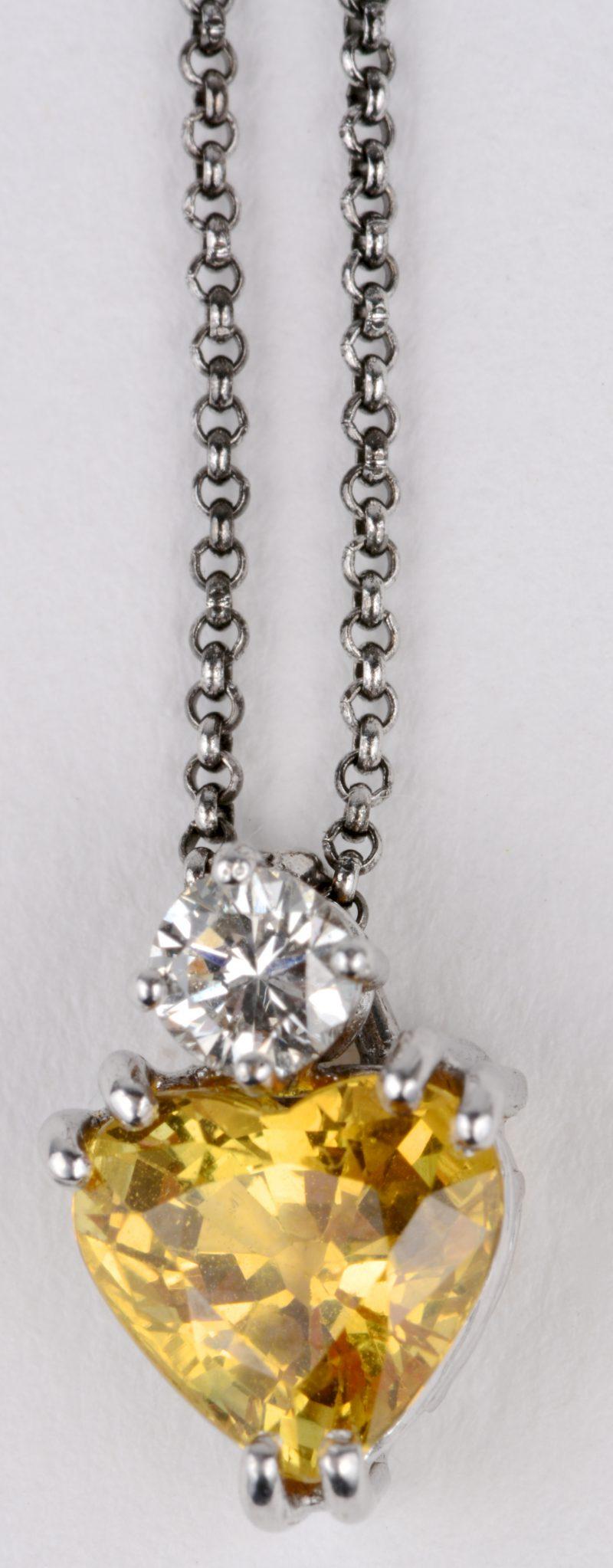 Een 18 karaats wit gouden gerodeerde ketting met hanger bezet met een briljant van ± 0,20 ct. en een hartvormige gele saffier van ± 2 ct.
