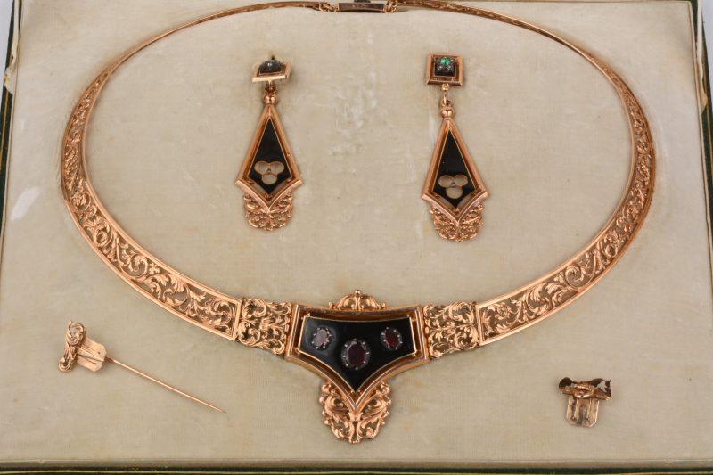 Een 18 karaats geel gouden in agourgewerkte parure, een  halssnoer en oorbellen waarin de stenen ontbreken. Een speld en sluitstuk zodat het middenstuk kan gedragen worden als broche, bezet met onyx en halfedelstenen. In originele doos.